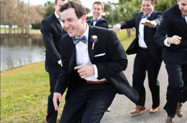 the groom and his groomsmen have some fun before the ceremony. the groom wore a boutonnière of one anemone highlighted with purple larkspur blooms.