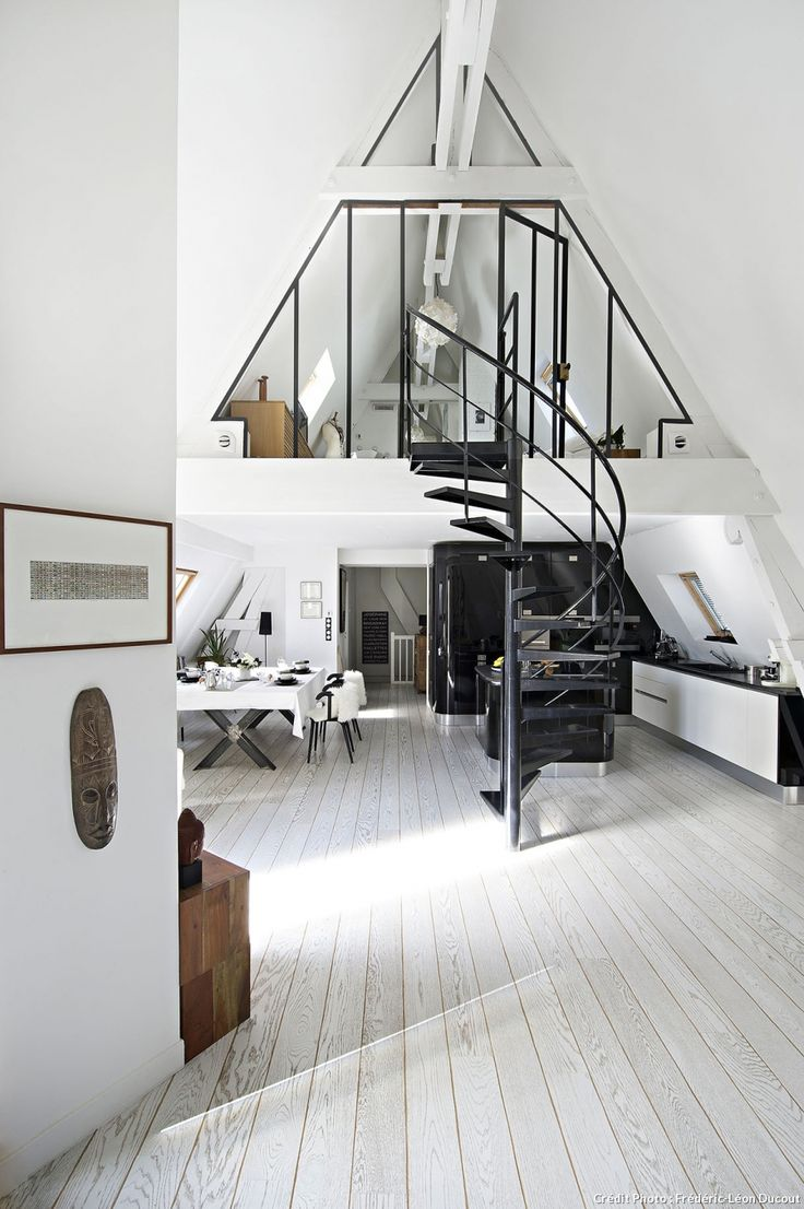 Loft in Paris kitchen and dining room in black and white. Love the spiral staircase in the middle.