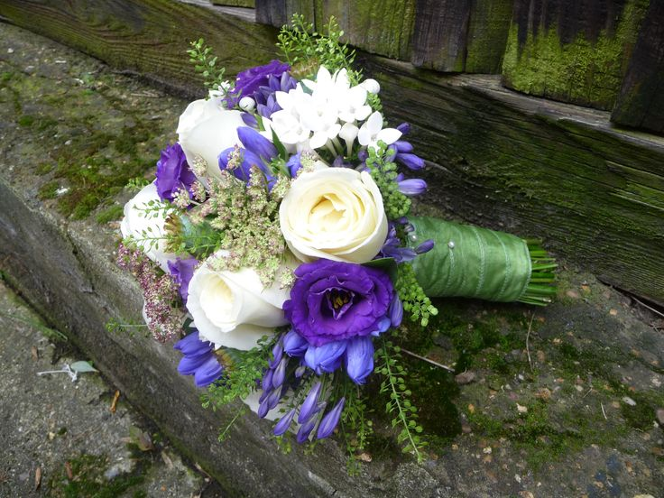 A bridal Bouquet of purple and white flowers, finished in a green ribbon.