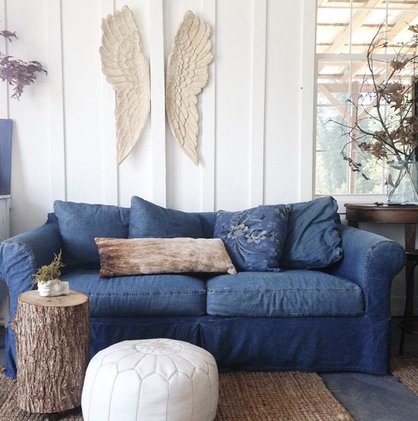 From the Nesting Place instagram a little shot of our 10 year old denim slipcovered sofa with the stump table on casters we made from a fallen tree, pouf and the signature piece in this photo is th...