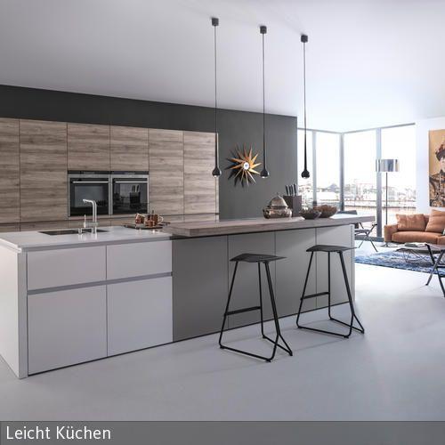 Beim grau-weißen Küchenblock sind die unterschiedlichen Arbeitsbereiche farblich voneinander abgegrenzt. Moderne schwarze Möbel und Accessoires wie Hängeleuchten …