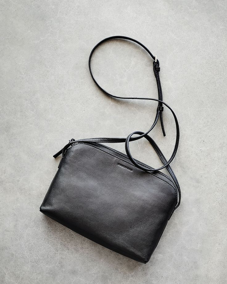 A simple cross-body bag with a minimalist design perfect for everyday wear. It has a top zip closure and two external mirrored compartments. #countryroadstyle