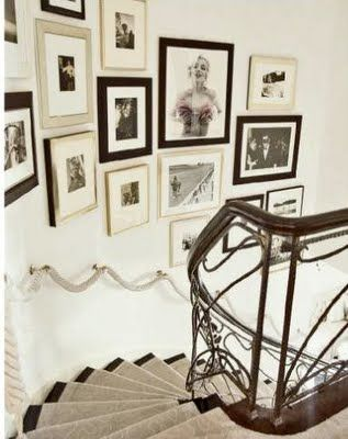 Black and white photos arranged so beautifully on the curved staircase. You CAN mix frame styles. The black and silver play well off of each other; mat treatment makes such a big difference too.