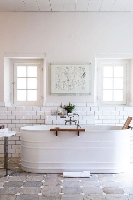 This bathtub comes from a livestock feed tank with a powder coating of crisp white paint, a vintage-inspired faucet, and wood shelf