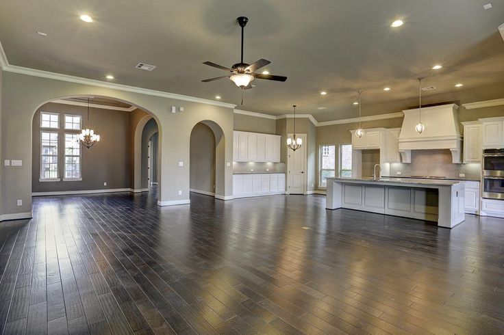 Darling home with a white kitchen with wood floors that opens to living room and dinning room and front door off in the back ground to the left.