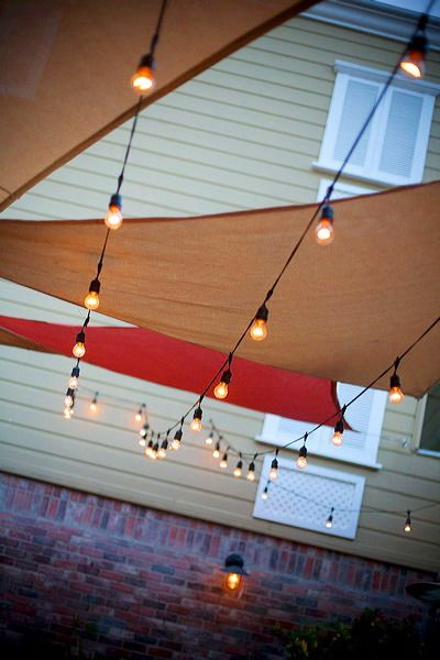 Patio string lights add flair below these sun canopy shades. Looks like medium base strings with suspenders: http://www.partylights.com/Commercial/Commercial-Medium-Strings-Bulbs