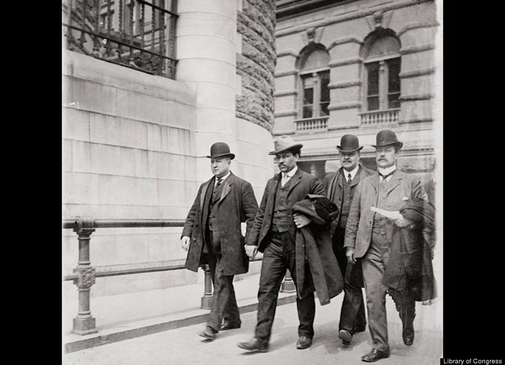 """This image, from 1903, shows detective Joe Petrosino (far left) with his colleagues Carey and McCafferty, escorting Thomas Petto (second from left) to prison. Petto, nicknamed the """"Ox,"""" was twenty-four and a member of the Morello gang. A pawn ticket found in his pocket tied him to the murder of Benedetto Madonia. Petrosino caught him a few days after the discovery of the body and suspected that Petto was the material author of the murder."""