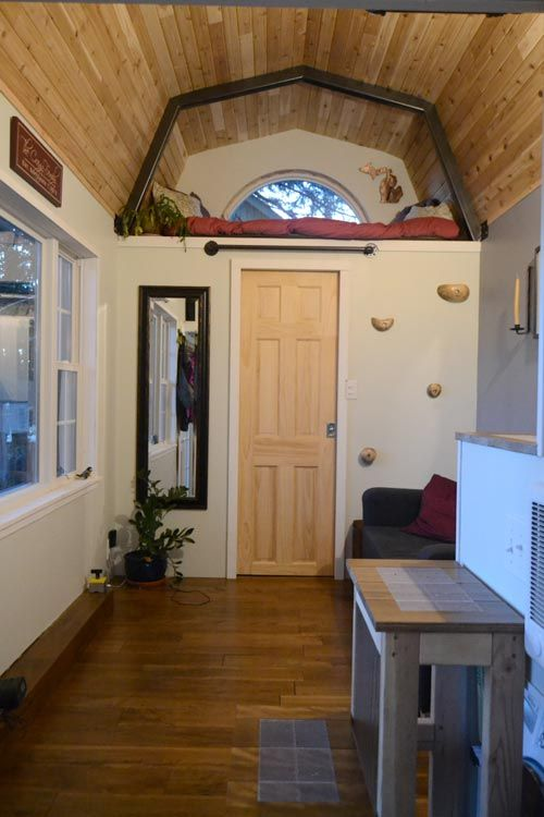 A 160 square foot cottage-style tiny house with elevated floors with trap doors, which allow for an extra 42 cubic feet of storage.