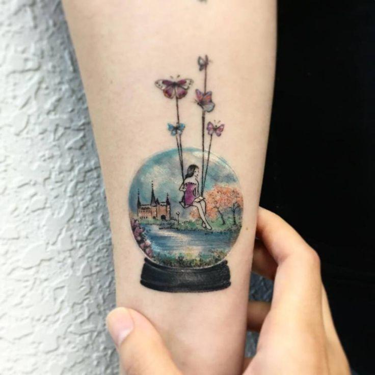 Illustrative snow globe tattoo on the inner forearm. Tattoo artist: Eva krbdk