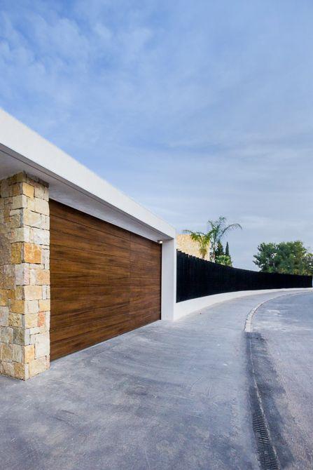 Puerta de garaje en madera y piedra en casa de diseño Cumbres | Chiralt Arquitectos Valencia