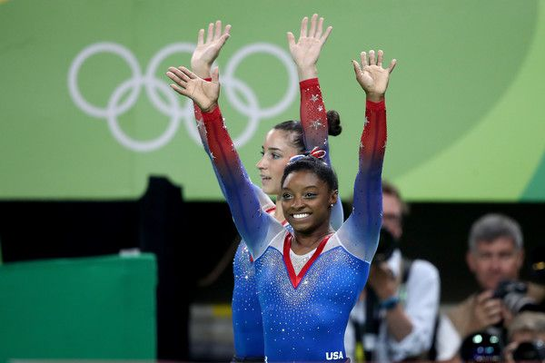 Simone Biles (R) and Alexandra Raisman (L) of the United States applaud fans after winning the gold and silver medals respectively after competing on the Women's Floor Final on Day 11 of the Rio 2016 Olympic Games at the Rio Olympic Arena on August 16, 2016 in Rio de Janeiro, Brazil.