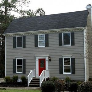 The siding is Benjamin Moore Sandy Hook Gray, the shutters are Benjamin Moore Kendall Charcoal, and the front door is Sherwin Williams Real Red