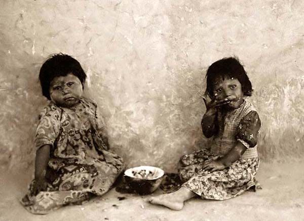 Two Hopi girls seated on the ground eating watermelons. These are very poor children. c 1900