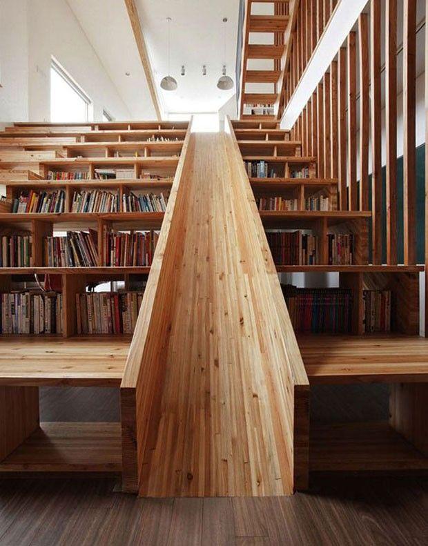 Uma escada com prateleiras de livros e um grande escorregador para crianças, de Moon Hoon
