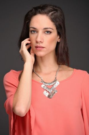 El collar Gahan está realizado en metal plateado. Su detalle de monedas metálicas en forma de V y piedra turquesa central con cadena le aportará brillo y textura a tu #look.
