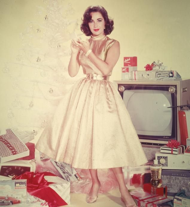 A publicity portrait shows Elizabeth Taylor in a yellow dress as she stands in front of an artificial Christmas tree amidst a pile of opened presents, including a television set, clothing, and a radio, circa 1950s.