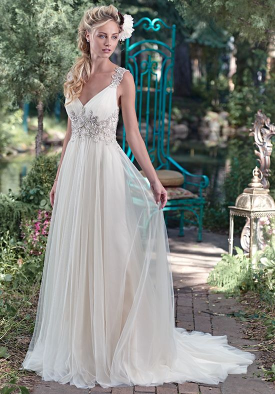 Romance is found in this stunning tulle sheath dress with plunging neckline and sparkling Swarovski crystal embellishment at the waist. Intricate patterns of beaded embroidery dance along the shoulder and lead to a dramatic illusion back. Finished with crystal button over zipper closure. Detachable tulle Watteau train sold separately.