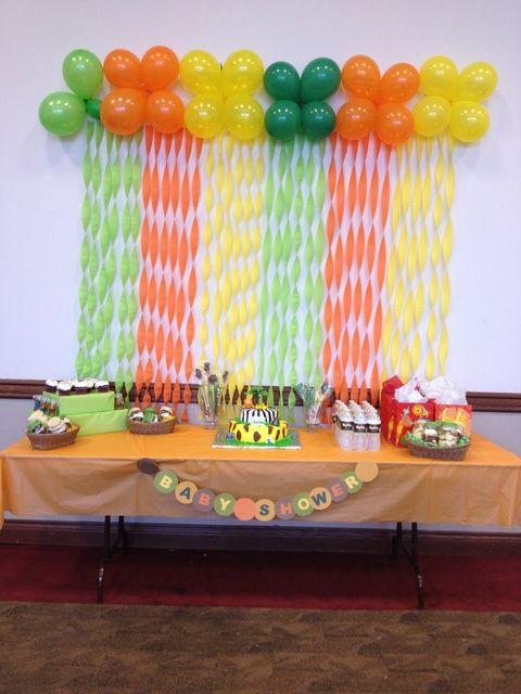 Coloridos globos y guirnaldas como fondo de mesa de postres para un baby shower.