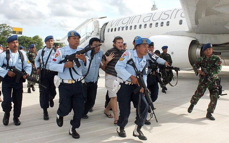 Australian Matt Christopher (centre) is escorted away by Indonesian military officers at Ngurah Rai International Airport in Bali, Indonesia, following a disturbance on a Virgin Australia flight