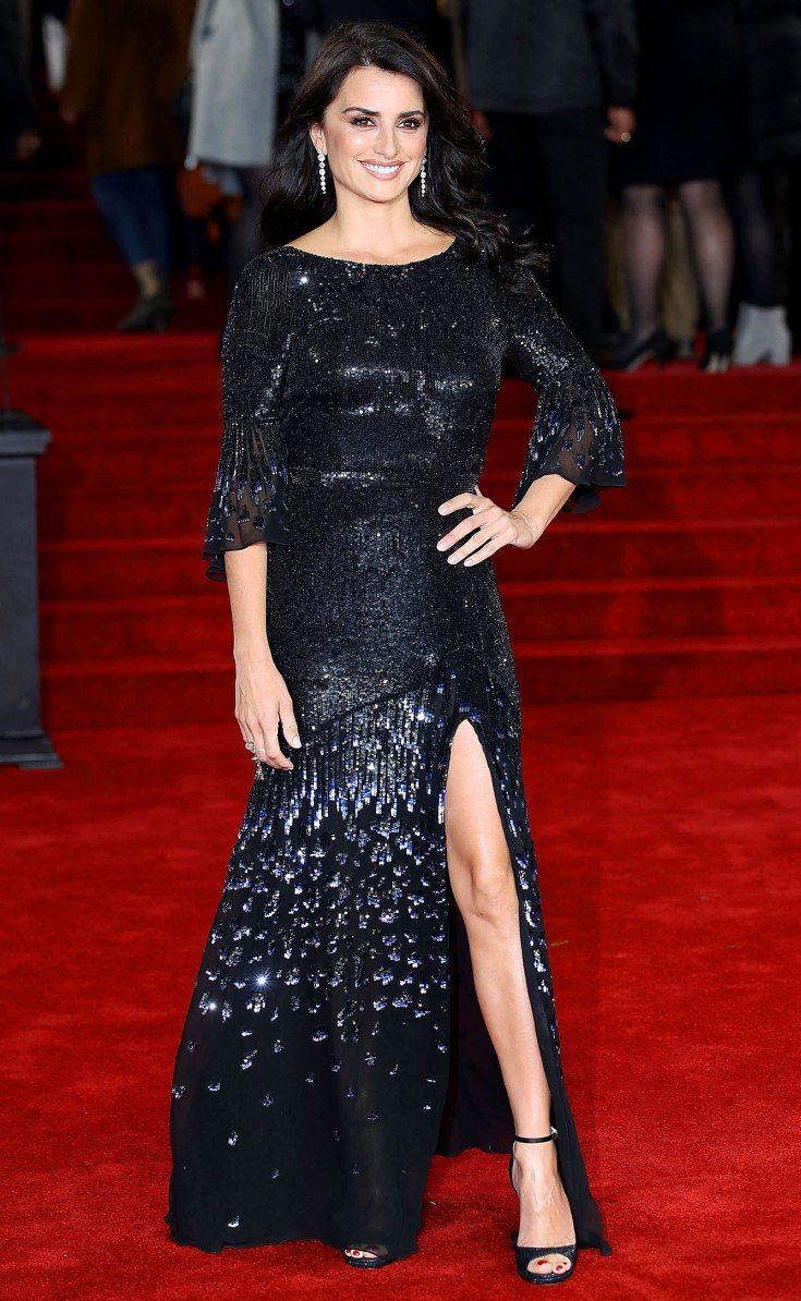 PENELOPE CRUZ wearing a black beaded bell sleeve Temperley London gown, Atelier Swarovski jewelry, and ankle-strap sandals at The Murder on the Orient Express premiere in London.