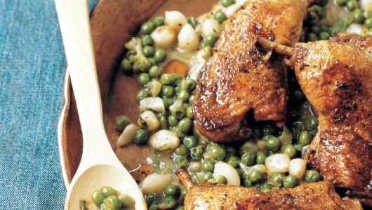 Muslos de pollo de corral con cebollas y guisantes estofados