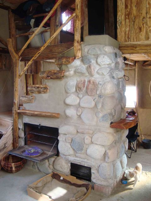 This masonry heater is designed into the center of a home and works as a normal fireplace until a damper is closed and the hot gases are forced through channels in the stone masonry which absorb and store the heat inside the building. The heater also serves as an oven, heats water and is a spiral staircase to the second floor.