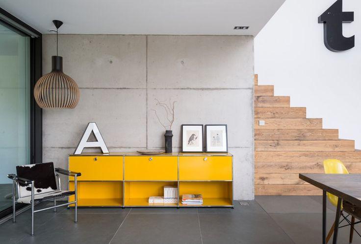 Die aus Blockstufen gearbeitete Eichentreppe bildet einen wohnlichen Kontrast zur Sichtbetonwand und zum dunklen Schieferboden. <a href=/bauen/schoener-wohnen-