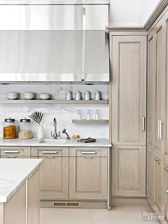 Perimeter cabinets made from alder wood get a thin coat of gray stain to warm up this transitional kitchen. The light wood cabinetry and open shelves contrast a riftsawn oak island stained a similar gray for subtle texture.