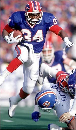 "Thurman Thomas / was an important part of the Bills ""no-huddle offense"" that won 4 consecutive AFC championships, but the Bills fell in the Super Bowl every year.  Thomas attended college at Oklahoma State University where he was a teammate of running back Barry Sanders.  Thomas currently holds the all-time Buffalo Bills rushing record with 11,938 yards and the team record for yards from scrimmage with 16,279 over 12 years. Hall of Fame 2007."