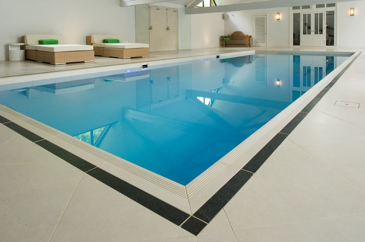 Minoli Tiles - Seastone - How is amazing this swimming pool tiled with Seastone White? Seastone Gradino special pieces for the step treads and Seastone Black cut to size for the darker border. Everything by #Minoli. Pool Internals: Seastone White 75 x 75 cm/ Pool Surrond: Seastone White 60 x 60 with Seastone Gradio (special pieces) for the surround step treads and with Seastone Black (cut to size) for the black border - https://www.minoli.co.uk/tiles/seastone-white/