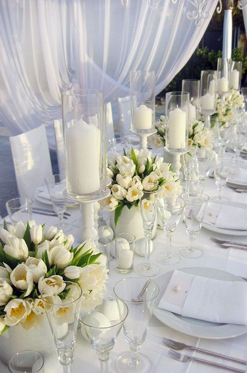 These delicate off-white tulips blend in flawlessly to this classic design. #WeddingCenterpieces