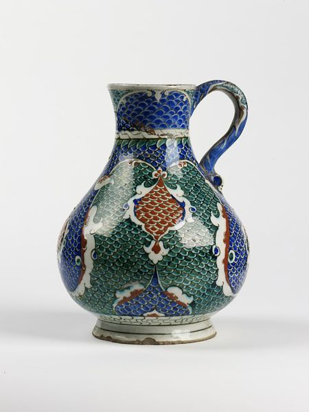Jug  Place of origin: Iznik, Turkey (probably, made)  Turkey  Date: ca. 1585-1600 (made)  Physical description  Jug of fritware, painted with a scale pattern in red, blue and green under a clear glaze.