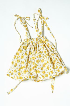 Dungaree Skirt In Yellow Rose 32.00 A brand new style for the season...dungaree skirts for children! A beautiful full, mid length skirt with full length tie-up straps. You can wear the straps crossed or straight. Then pull the garment higher and it's worn as a smock top with oversized ribbon ties. Extremely versatile and creates two completely different looks. Wear as a top with bloomers for a truly vintage original look. Our new crush.
