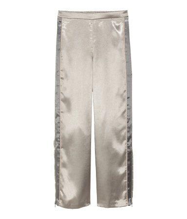Silber. Hose aus weichem Webstoff mit Kontraststreifen an den Seiten. Die Hose hat eine Stretchpartie hinten am Bund und eine Potasche mit Reißverschluss.