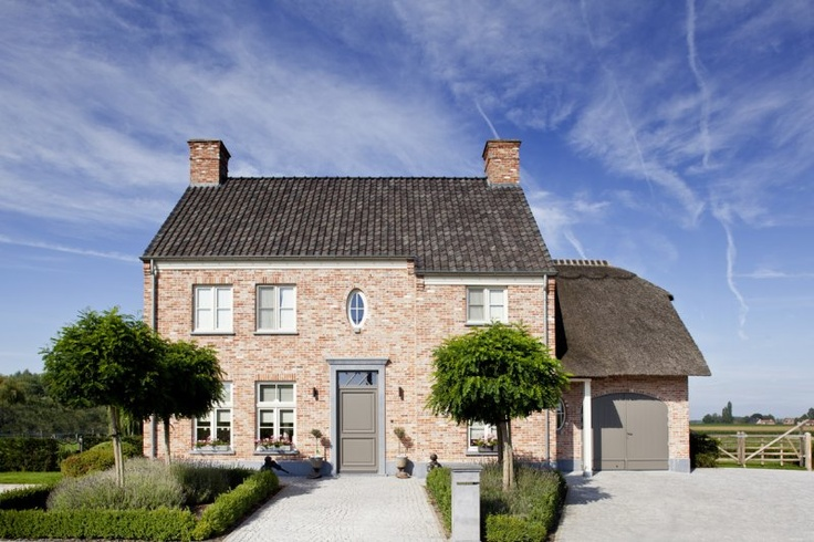 Home in country style with typical front door, the oval window and the attached garage with thatch roof    http://www.gruwez.org