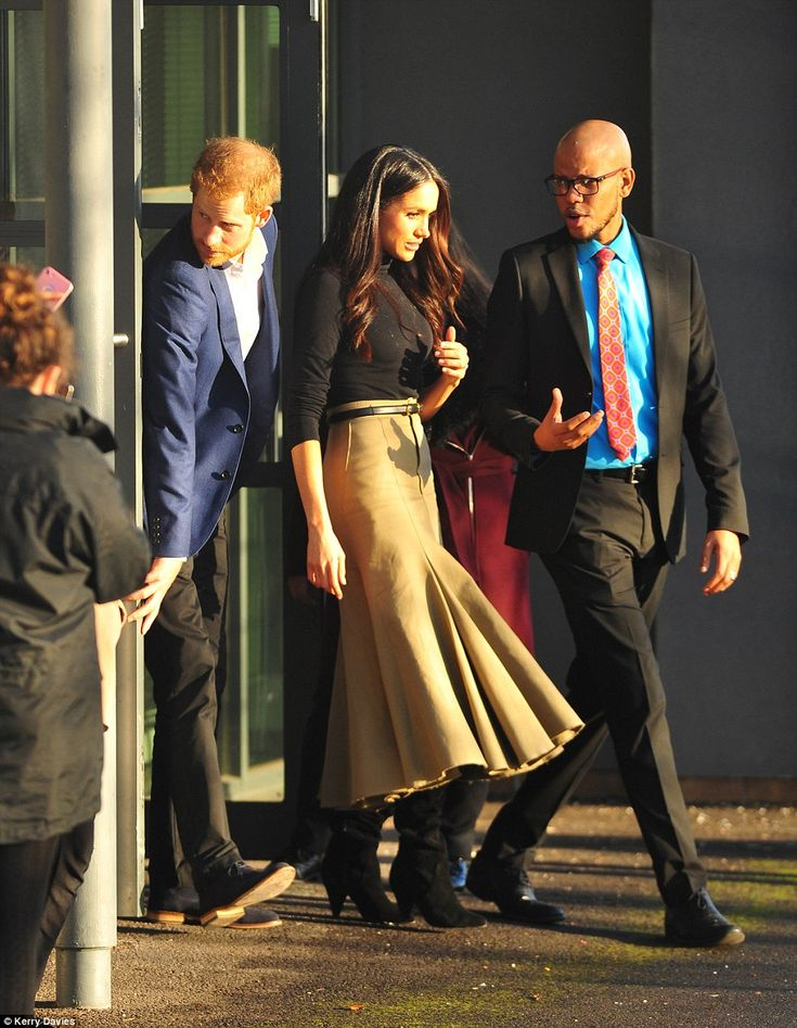 Harry opens the door for Meghan on their visit to the Nottingham Academy as his fiancee speaks to a member of staff