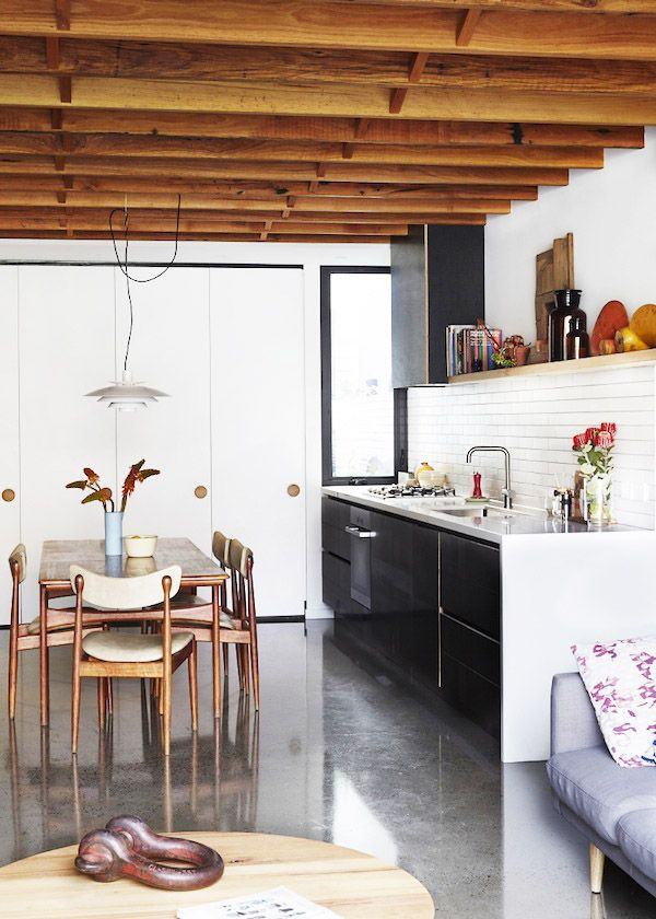 Every square inch of this small cottage in Fitzroy North is packed with  vintage charm and inspiring architectural details. The use of exposed beams  in the ceiling offers the perfect contrast to the simple kitchen and eating  area and flows nicely with the egress to the backyard. The vintage pos
