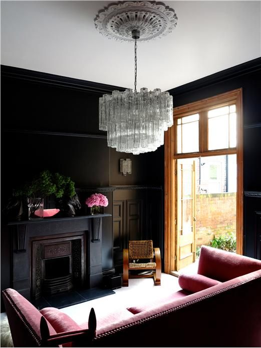 Black paneling and a pink mohair sofa