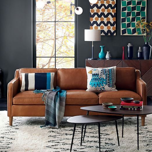 dark color wall, brown leather sofa, nesting coffee table, colorful art and vases, white rug