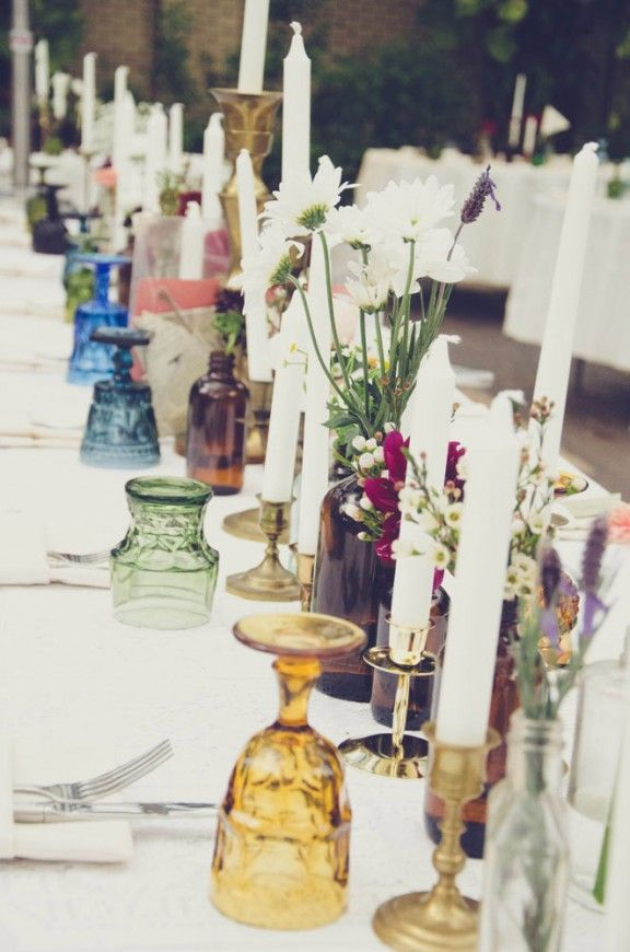 colorful tablescape with brass candle holders and vintage colored glass goblets boho bohemian wedding reception