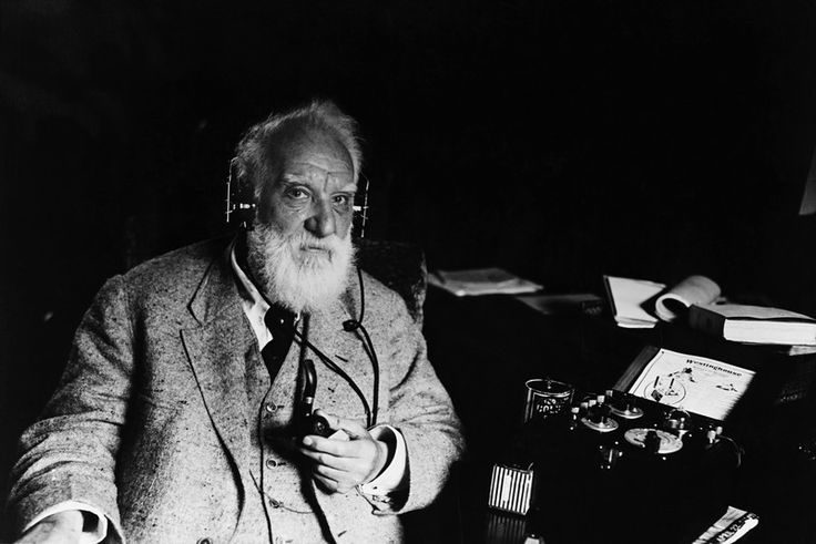 Portrait of Alexander Graham Bell (1847-1922), inventor of the telephone.  He wears headphones that are attached to a piece of electrical apparatus