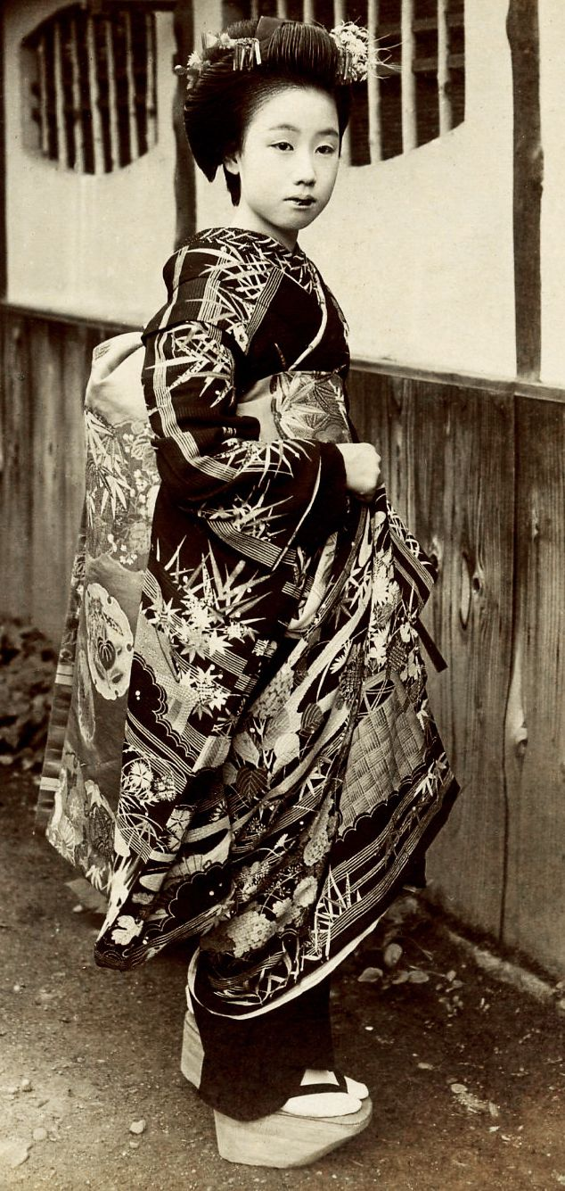 """Hand-colored photo, 1920's, Japan. """"A Maiko (Apprentice Geisha) dressed in a black,ceremonial kimono, with special tortoiseshell Kanzashi in her hair and double bira-kan (fluttering hair ornaments). Text and image via Blue Ruin 1 of Flickr"""