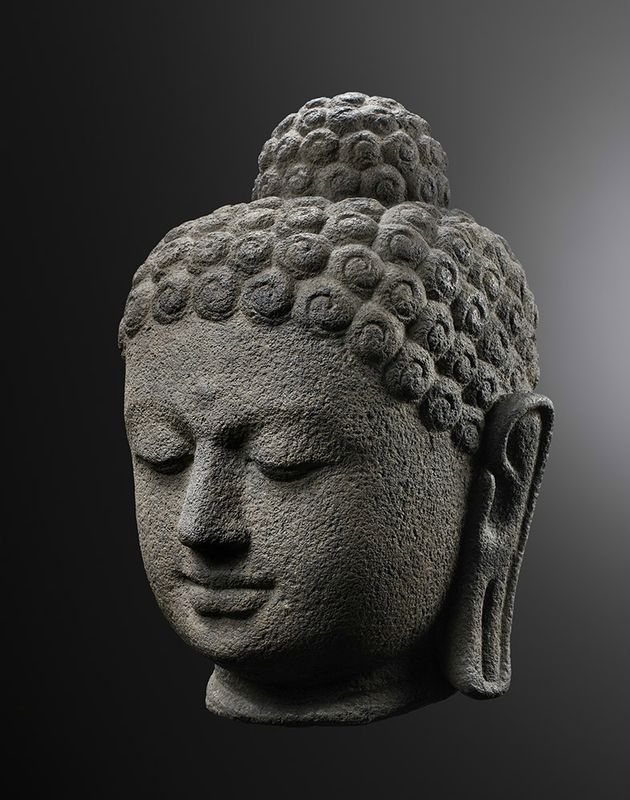 Volcanic Stone Head of Buddha Shakyamuniva. Indonesia, Central Java, 9th-10th century. Height: 15 inches (38 cm). Photo: Studio Roger Asselberghs - Frédéric Dehaen. © Gisèle Croës