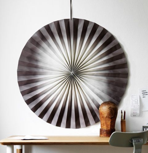 A large black and white paper wall decoration hanging on a white wall above a table.