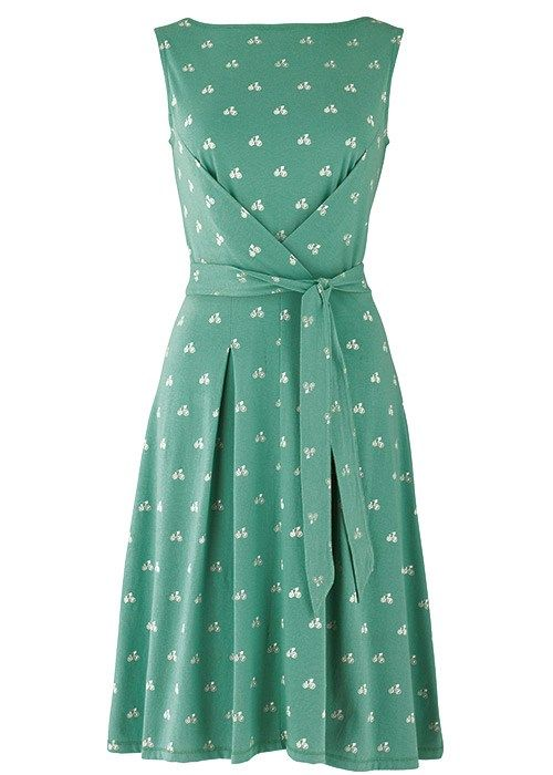 FRANCESCA BOW DRESS IN BICYCLE PRINT  £60.00  DESCRIPTION    Bicycle print sleeveless fit and flare jersey dress in pistachio. Cross-over front and swing skirt with inverted box pleats. Self-tie bow belt. Made in India in 100% organic cotton.