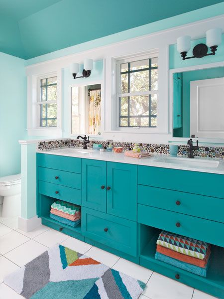 What a fun bathroom for the kids with bubble tile, turquoise color, and built-in step stools under the double sink!