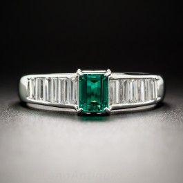 Sleekly tailored in platinum, this streamlined jewel centers on a diamond bright, and almost diamond clean, crystalline green emerald-cut emerald weighing .39 carat. The gemmy gemstone glistens between gently tapered rows of seamlessly-set baguette diamonds, totaling .58 carat, set flush into the top half of the ring. A lovely right-hand ring or alternative engagement ring. Currently ring size 6 1/4.