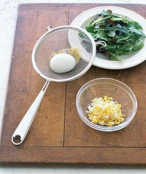 Crumble hardboiled eggs for a salad topping by pushing them through a mesh strainer.