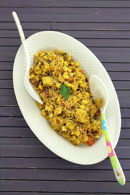 Corn chaat recipe - boiled sweet corn kernels are mixed with boiled potatoes, onion, tomato. Drizzled green chutney and sweet chutney on top and garnished with thin sev.