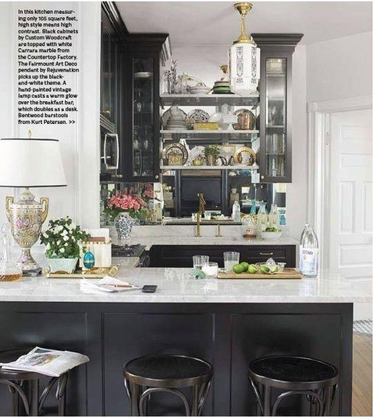 Black cabinets. Light counter tops. Wood floor.